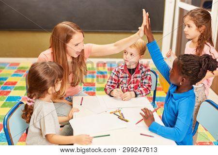 Teacher or kindergarten teacher and a girl give themselves a high five in kindergarten