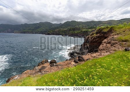 Flowers Dot The Hillside Above A Volcanic Coastline In Ponta Delgada On The Island Of Flores In The