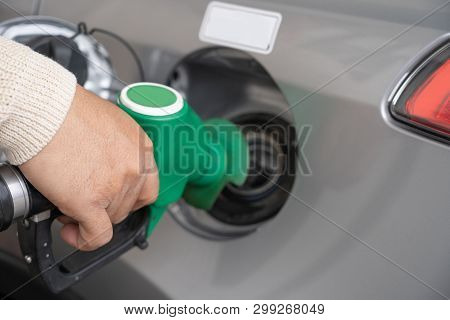 Hand Refilling The Car With Fuel At The Refuel Station. Grey Car At Gas Station Being Filled With Fu