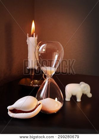 Still Life With Vintage Sandglass, Small Toy Elephant, White Shell And Burning Candle Against A Low