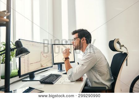 Busy Working. Handsome Bearded Trader In Formal Wear And Eyeglasses Is Analyzing Trading Charts And