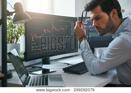 Successful investor. Serious young male trader holding eyeglasses and analyzing data and graphs on his laptop while working in his modern office poster