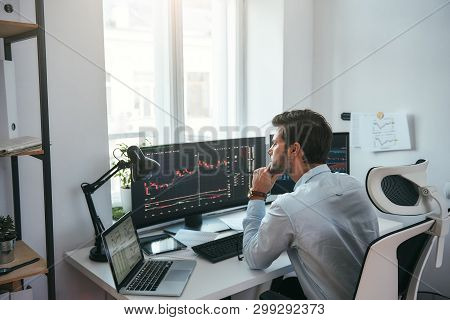 Trading On World Markets. Young Stock Market Broker Analyzing Data And Graphs On Multiple Computer S