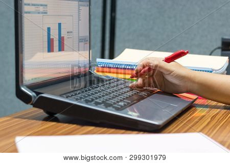 Teacher Hand Holding Red Pen For Checking Students Homework Assignment On Notebook Keyboard With Bar
