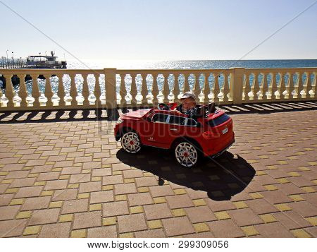 A Little Blond Boy Rides A Red Typewriter Along The Black Sea Embankment