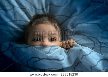 Boy In Bed With His Eyes Open. The Child Is Afraid Of The Dark. Tormented By Nightmares And Terrible
