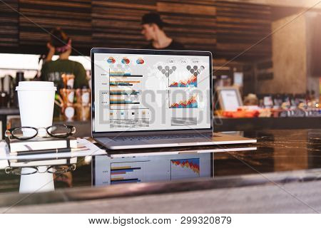 Close Up Of Laptop With Graphs, Charts On Screen, Notebook, Cup Of Coffee On Table In Empty Cafe Wit