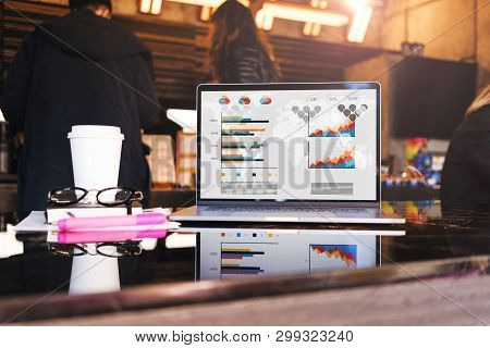 Close Up Of Laptop With Graphs, Charts, Schedule On Screen, Notebook And Cup Of Coffee On Table In E