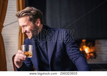 Handsome smiling man with a drink. poster