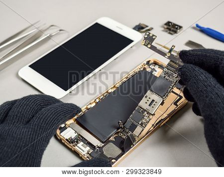 Technician Or Engineer Disassembling Components Broken Smartphone And Take Off Logic Board For Repai