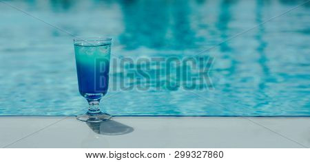 Blue Coctail With Ice In The Glass On The Swimming Pool Background. Resort Tropical Hotel In Summer