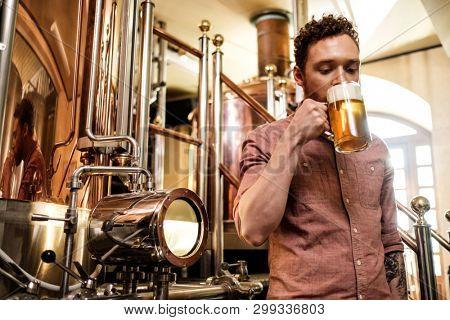 Man tasting fresh beer in a brewery