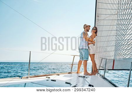 Smiling young couple traveling on vacation sailing on open sea ocean enjoying romance.