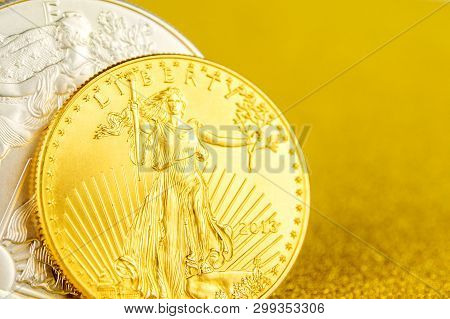 Closeup Of Silver Eagle And Golden American Eagle One Ounce Coins On Golden Background Placed On Lef