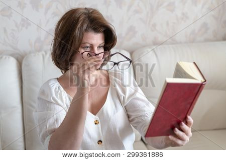 Woman With Impaired Vision Reading A Book Through Two Glasses
