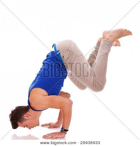 barefoot casual man doing a handstand on white background. young bboy in a difficult dance move. dancer standing on his hands
