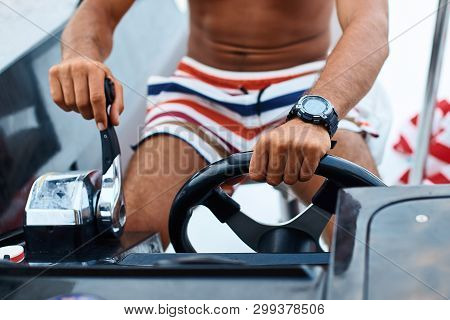 Tanned Young Handsome Captain Or Skipper Steering At The Helm And Control Panel Of A Yacht With His