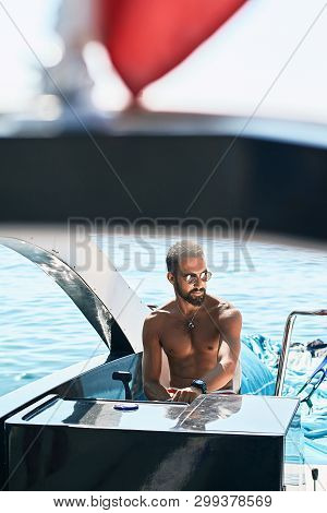 Tanned Young Handsome Bearded Muslim Captain Or Skipper Steering At The Helm And Control Panel Of A