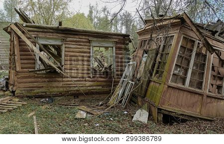 Old Abandoned And Destroyed Log House In Russia. Abandoned House In The Middle Of The Forest