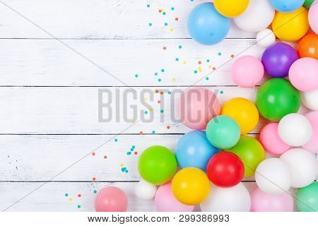 Heap Of Colorful Balloons And Confetti On White Table Top View. Festive Or Party Background. Flat La