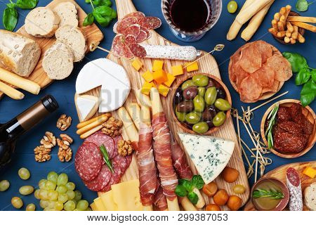 Italian Appetizers Or Antipasto Set With Gourmet Food On Kitchen Table Top View. Mixed Delicatessen