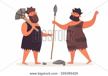 A Primitive Man With An Ax Is Talking Beside A Man With A Spear. Prehistoric People Dressed In Pelts