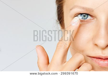 Young Woman Puts Contact Lens In Her Eye Over White Background. Eyewear, Eyesight And Vision, Eye Ca