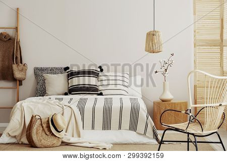 Striped Bedding On Comfortable King Size Bed In Contemporary Bedroom Interior With Wicker Chair And