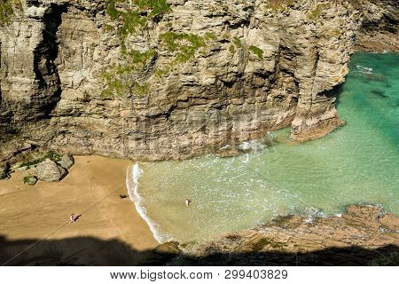 Two Small Girls And Dog Playing On Beach And In Sea Near Tintagel, Cornwall, England, Uk