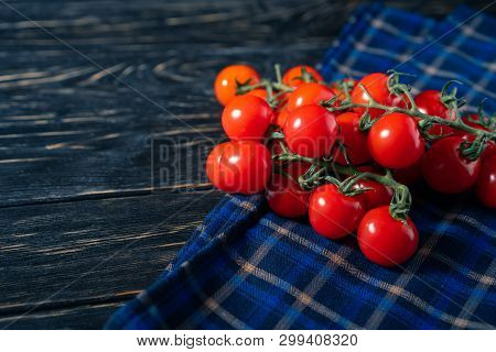 Cherry Tomatoes In The Checkered Cloth Serviette On The Dark Wooden Table. Juicy Ripe Vegetables On