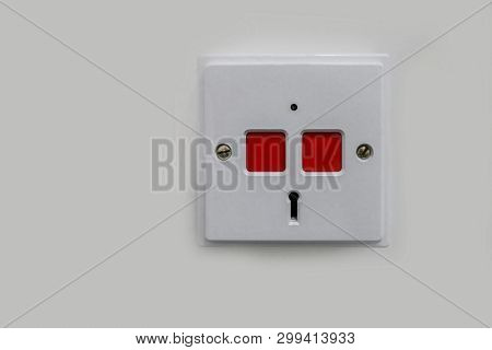 White Plastic Panic Panel With Two Red Square Push Buttons And A Key Hole To Reset.  Push Here In An