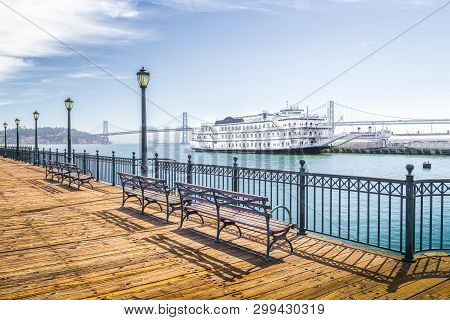 Benches At Historic Pier 7 With Traditional Paddleboat And Oakland Bay Bridge In The Background On A