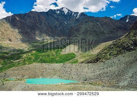 Turquoise Water Of Mountain Lake Near Huge Rocky Mountain Range With Snow. Huge Clouds In Blue Sky A