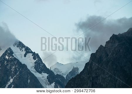 Low Cloud Before Huge Glacier. Giant Snowy Rocky Mountains Under Cloudy Sky. Thick Fog In Mountains