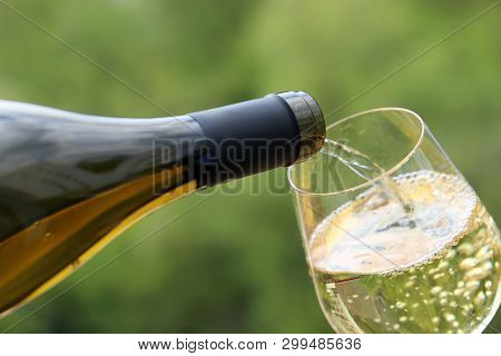 White Wine Pouring From The Bottle Into The Glass On Green Nature Blurred Background. Concept Of Cel