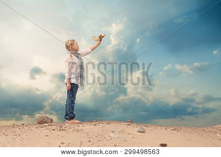 Small Girl Playing With A Toy Airplane Against The Blue Sky