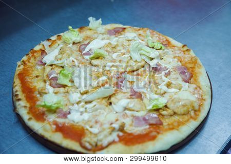 pizza with chicken ham and mozzarella freshly cooked on a board