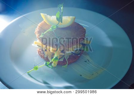 meat hamburger with french fries and pickled cucumbers decorated piece of lemon