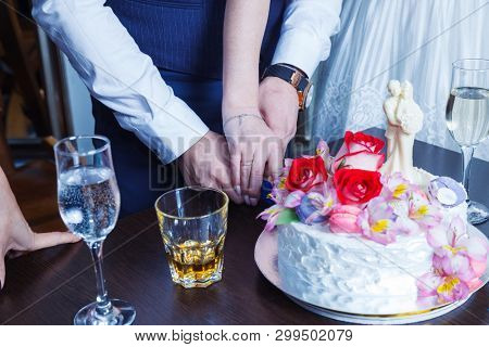 Bride and groom cut the celebratory cake decorated with flowers and cream on the table