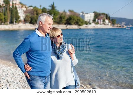 Senior Couple Is Hugging And Walking At Sea Beach Outdoor. Happy Man And Woman Are Relaxing, Traveli