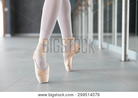 Ballerina Is Dancing In Ballet Pointe Shoes. Close Up Of Legs. Girl Has Workout In Ballet Class Room