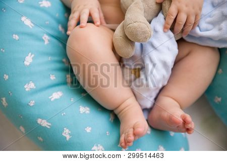 The Bare Feet Of A Cute One Year Old Baby Lying On A Special Pillow For Breastfeeding. A Toy In The