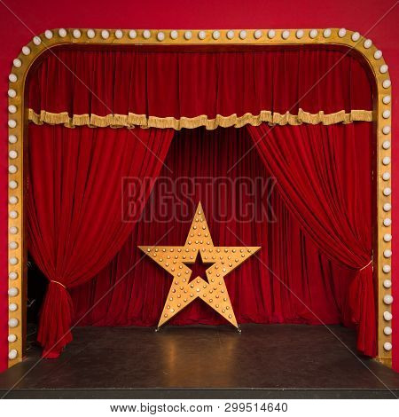 Improvised theatrical stage with a red velvet curtain and a big star with luminous lights. Concert hall. Star performance poster