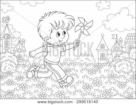 Little Boy Running And Playing With His Toy Whirligig Among Flowers Against A Background Of Houses O