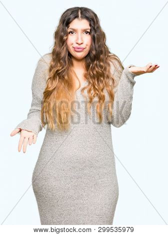 Young beautiful woman wearing winter dress clueless and confused expression with arms and hands raised. Doubt concept.