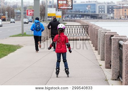 St. Petersburg, Russia - May 02, 2019: Young Girl On Roller Skates In Protective Gear Rides Along Th