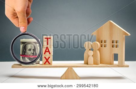 Wooden House And Family With The Inscription Tax On The Scales. Taxes On Real Estate, Payment. Penal