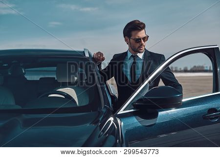 Luxury Style. Handsome Young Businessman Entering His Car While Standing Outdoors