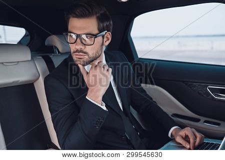 Thinking About Business. Thoughtful Young Man In Full Suit Working Using Laptop And Adjusting His Ey
