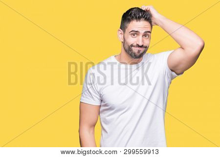 Young man wearing casual white t-shirt over isolated background confuse and wonder about question. Uncertain with doubt, thinking with hand on head. Pensive concept.